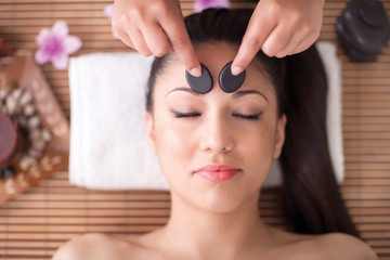 Beautiful woman having a wellness head massage with stones