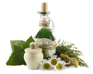 Bottle with green remedy and healing herbs