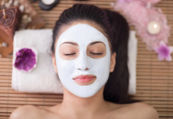 Spa therapy for young woman having facial mask at beauty salon