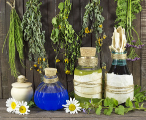 Healing herbs with glass bottles on wooden shelf