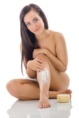 woman putting cream on her legs