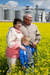Elderly couple with grandchild on rapeseed field