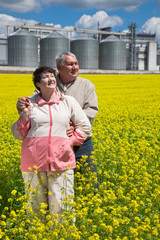 Elderly couple on rapeseed field