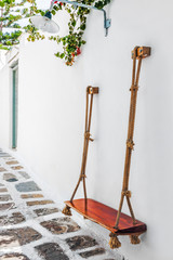 Swing seat fixed on wall in a narrow lane of Mykonos