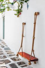 Swing seat fixed on wall in a narrow lane of Mykonos