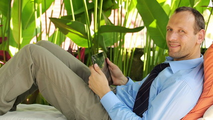 Happy businessman with tablet computer at luxury gazebo in garde