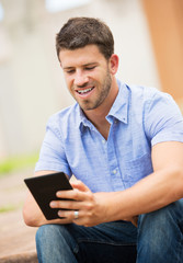 Young man reading E-book outside