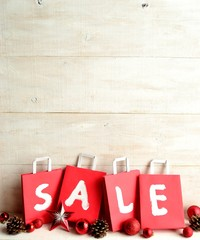 Red bargain sale shopping bags with Christmas ornaments