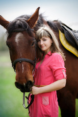 Portrait of the beautiful girl with a brown horse in park