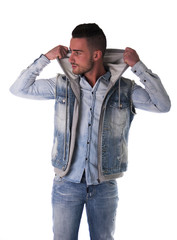 Handsome young man in hoodie, denim vest and jeans