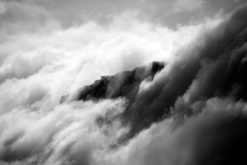 Black and white cliff appearing through clouds