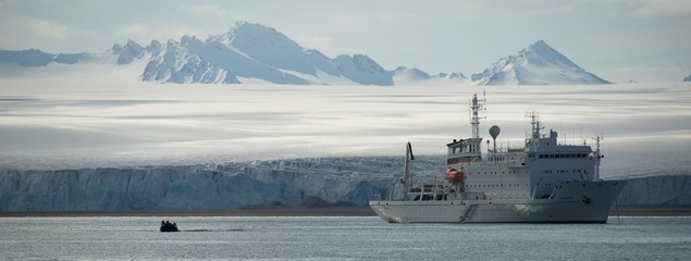inflatable and white ship beside ice cliff