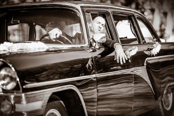 Cheerful groom at a wheel of a black old retro of the car