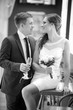groom with a glass of champagne and the bride with a bouquet
