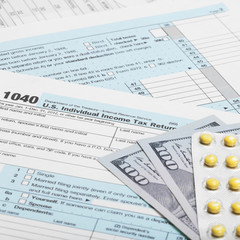 US Tax Form 1040 with dollars and pills - 1 to 1 ratio