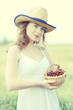 Beautiful young woman holding wicker basket with cherries in