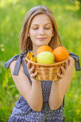 portrait of woman holding basket with fruits