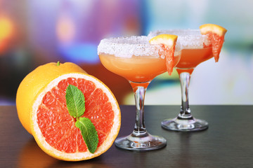 Grapefruit cocktail in glasses on bright background
