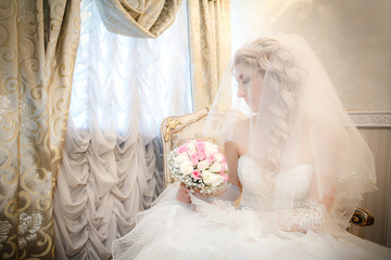 Portrait of the bride  sitting on a sofa near a window