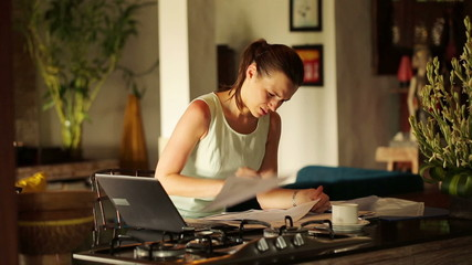 Angry, overwhelmed businesswoman reading documents by table