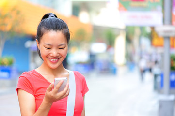 young asian woman use her cellphone on shopping street