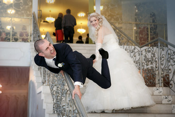 Happy bride and groom play the fool on ladder