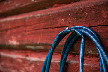 Blue hose hanging from a nail