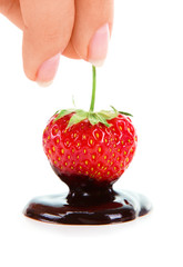 Woman hand holding chocolate-dipped strawberry