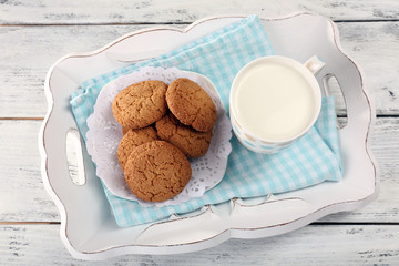 Milk and cookies on tray on table