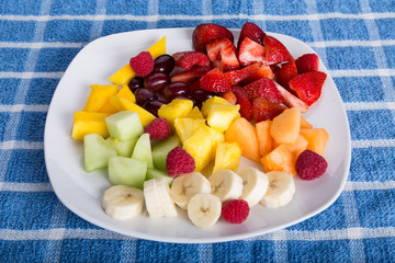 Cut Tropical Fruit on White Plate and Blue Towel