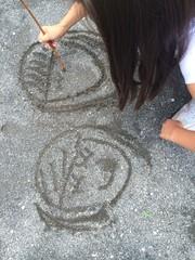 地面に絵を描いている女の子