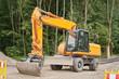Strassenbau - Ein grosser oranger Bagger vor einem Wald