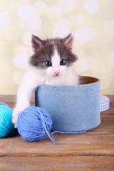 Cute little kitten in box playing with thread ball,