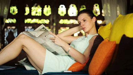 Businesswoman reading newspaper, relaxing sofa at home