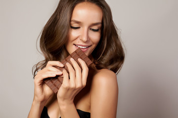 Portrait of girl holding a chocolate bar feeling temptation