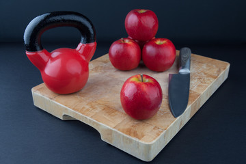 Red apples, knife, and kettlebell on chopping board