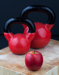 Red apple and kettlebells on chopping board