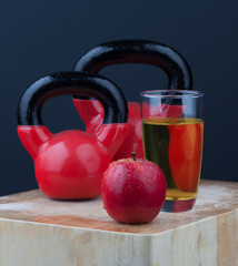 Red apple, juice, and kettlebells on chopping board