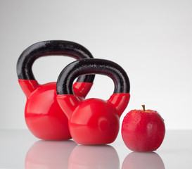 Red apple and kettlebells on reflective surface