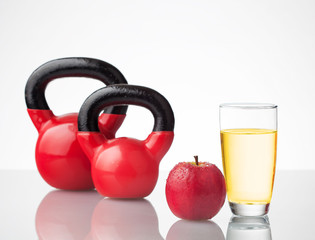 Red apple, juice, and kettlebells on reflective surface