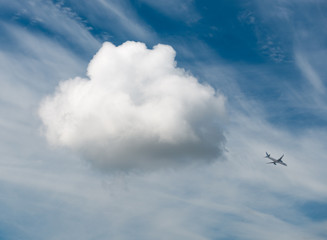 White cloud in the blue sky and a airplane
