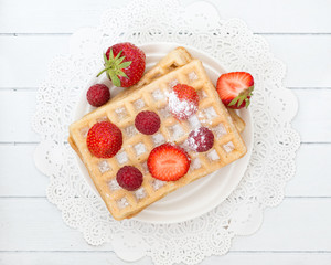 Delicious waffle with fresh berries for breakfast on wooden whit