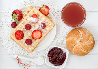 Delicious waffle with fresh berries and jam for breakfast on woo