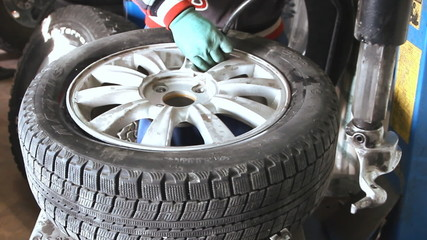 Mechanic inflating car tire closeup