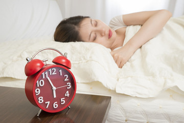Woman sleeping in bed beside alarm clock