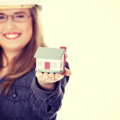 Young beautiful business woman with house model