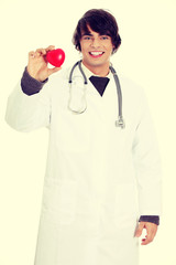 Happy handsome young male doctor holding heart.