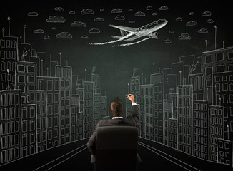 Businessman sitting in front of a cityscape drawing on a chalkbo
