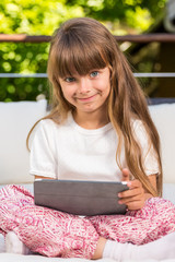 Young girl sitting with tablet
