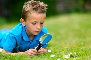 Boy with magnifying glass in garden